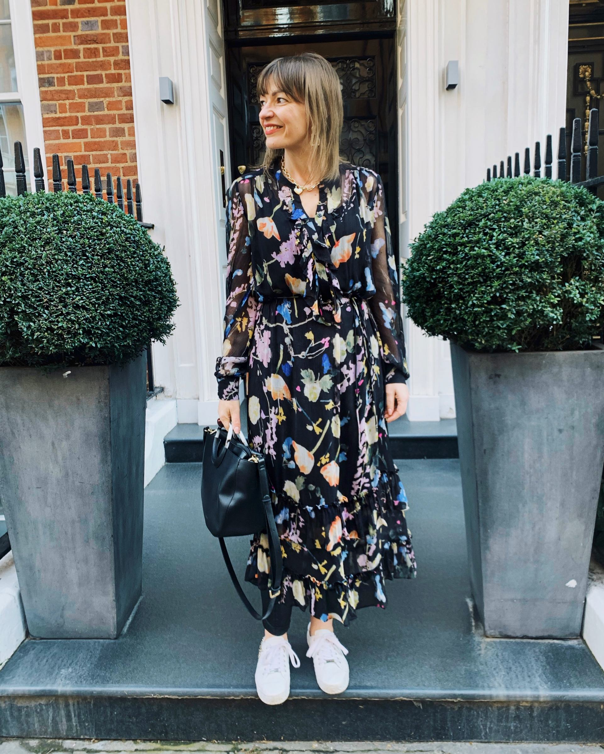 Lizzi wearing a dark floral dress with faux leather leggings and styled with white trainers, a black tote bag and a gold chain necklace.