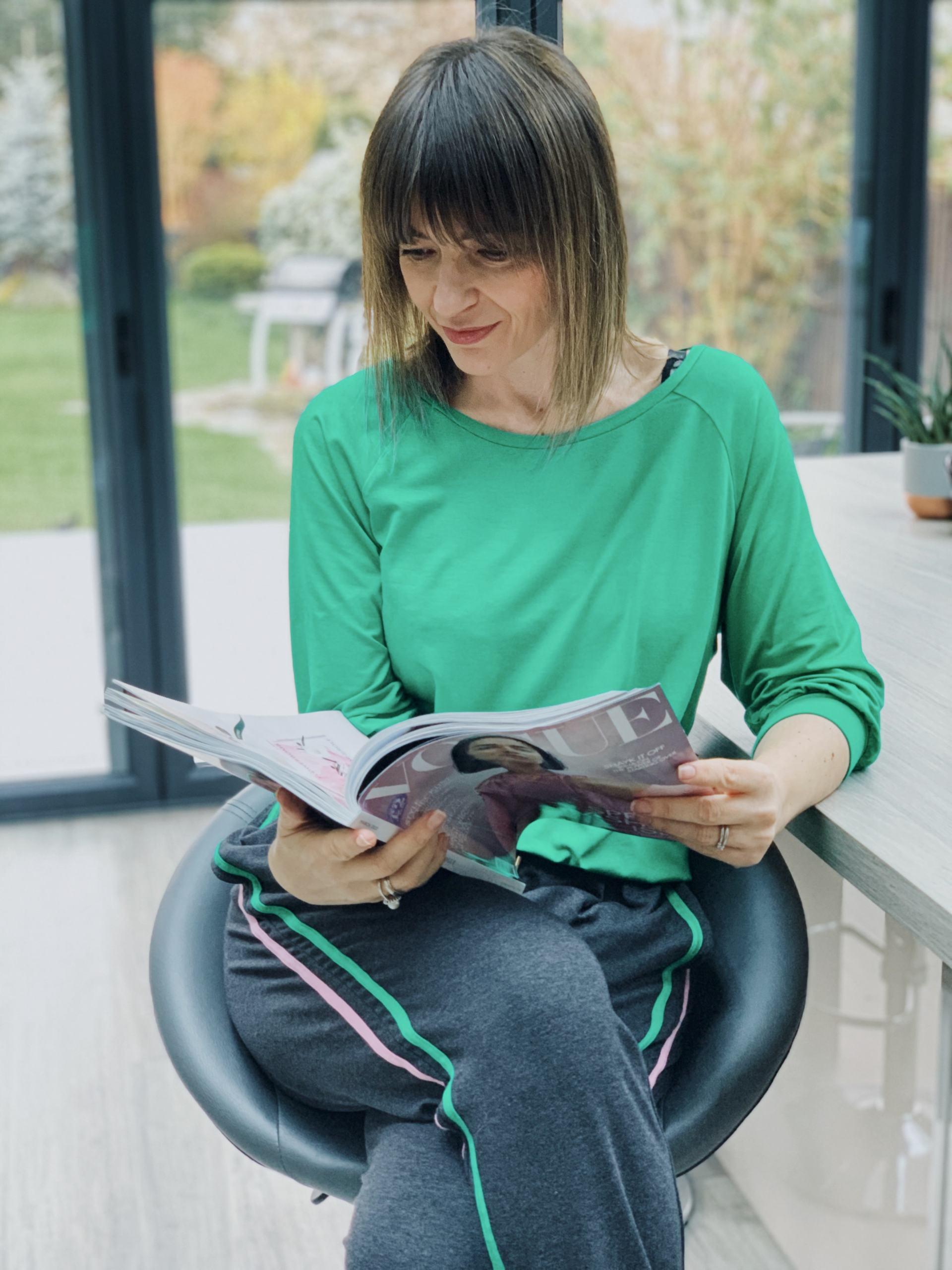 Lizzi sitting on a bar stool reading a magazine