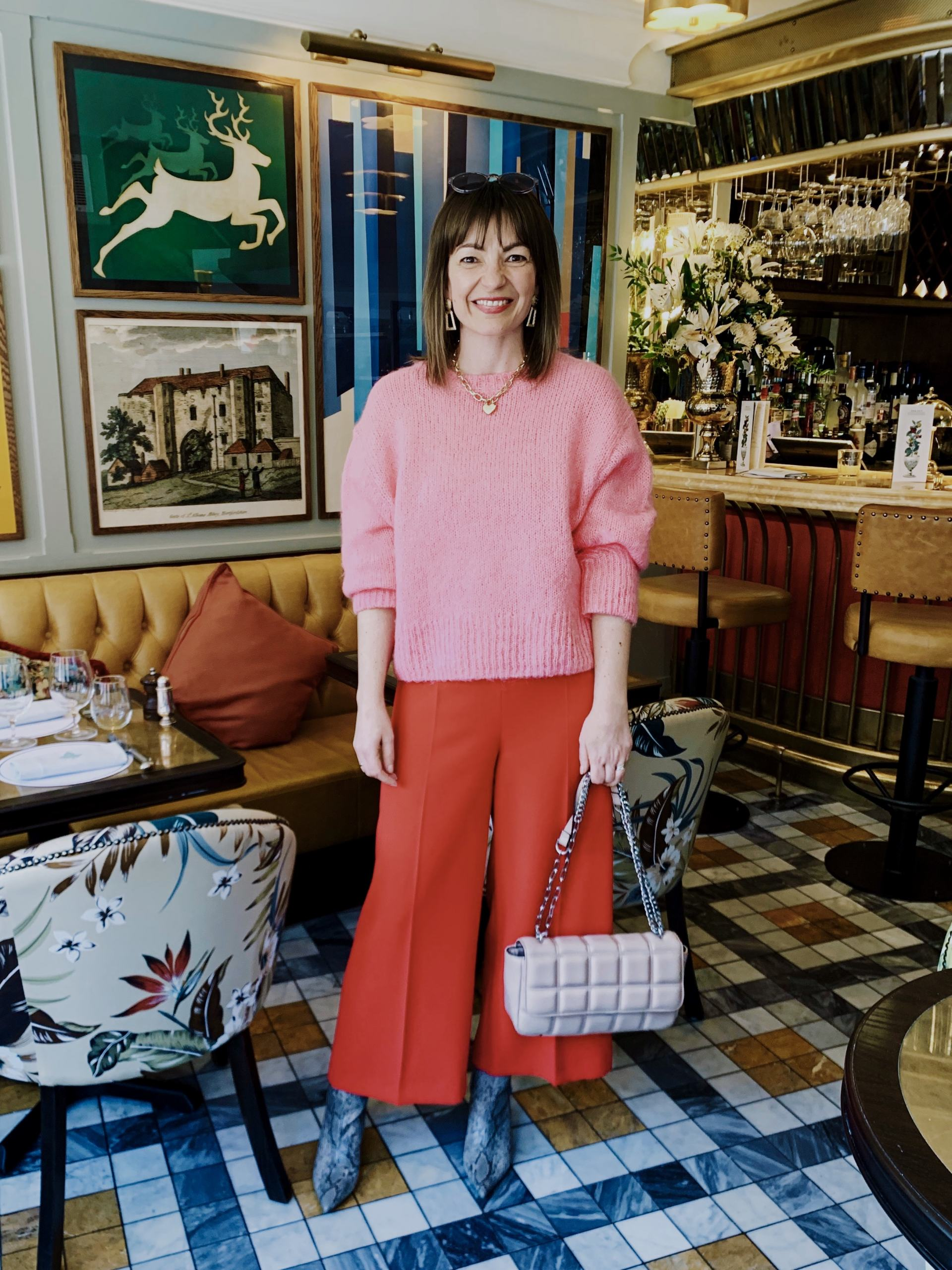 pink jumper with red trousers in ivy restaurant