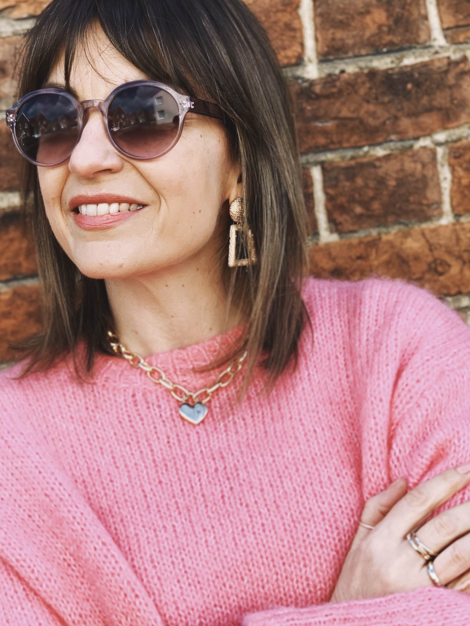 Sunglasses with pink jumper and gold statement jewellery