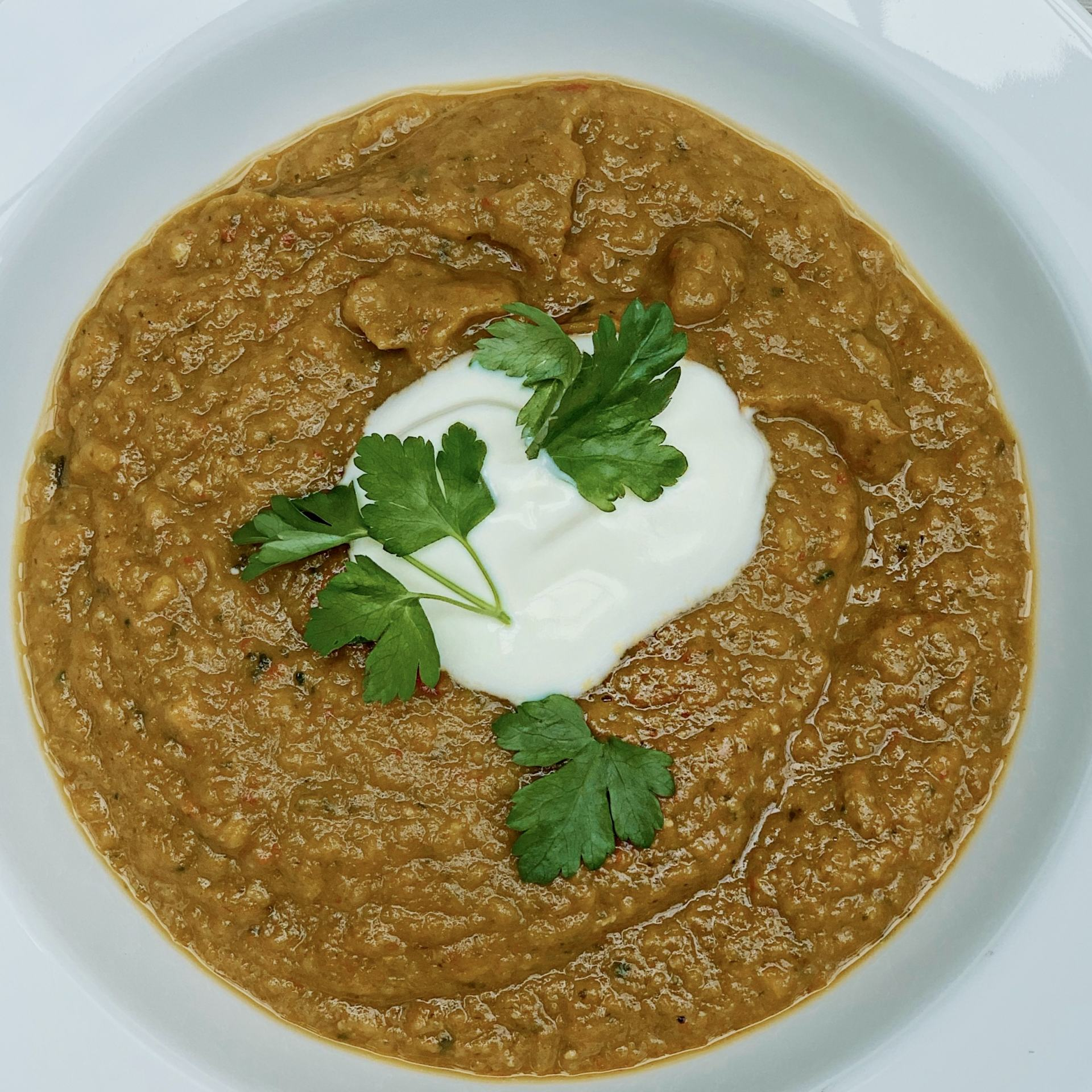 A white bowl with vegetable and lentil soup with natural yogurt and coriander