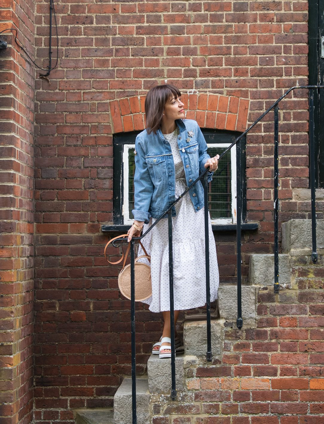 Lizzi on staircase wearing a white summer dress