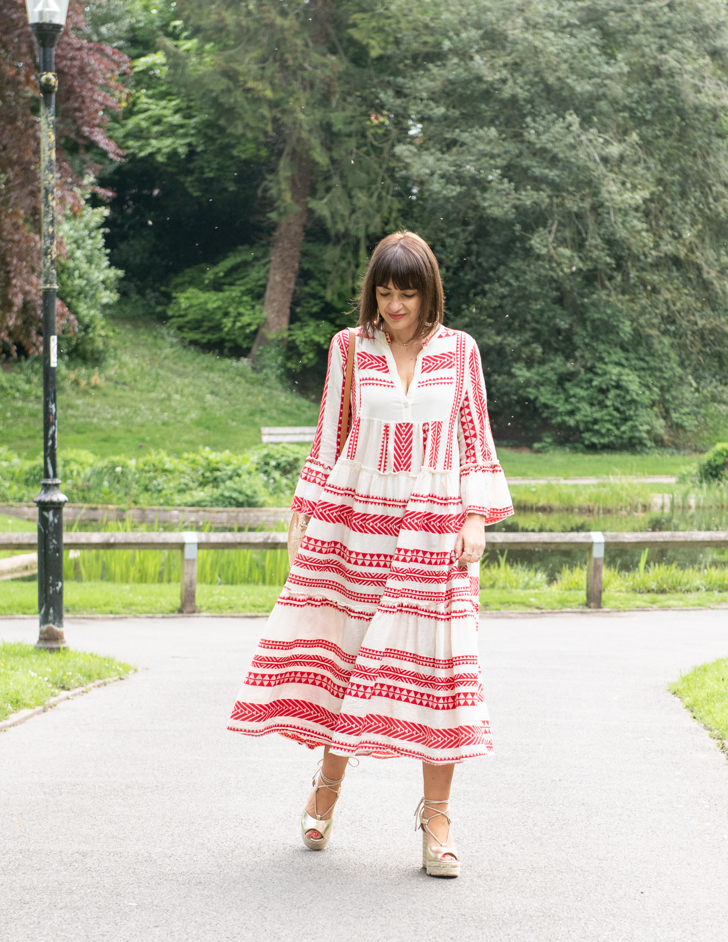 The Aztec dress in red and cream worn by Lizzi, style blogger to Loved by Lizzi - she is standing in a park wearing it with a straw bag and espadrilles