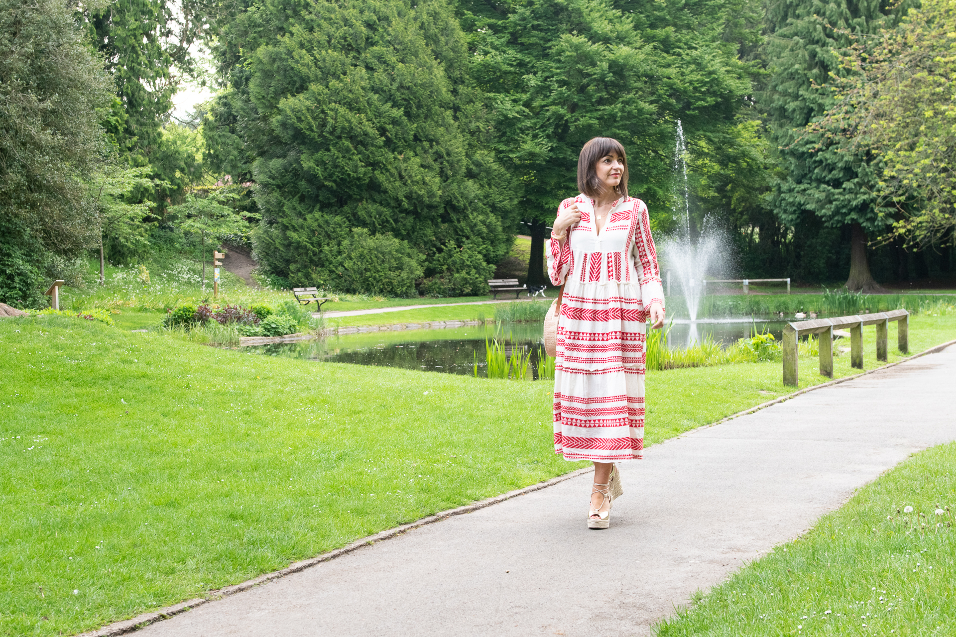 The Aztec dress. A red and cream cotton dress that is perfect for summer 2021. Worn here in a park to showcase how it looks great with a straw bag and espadrilles.